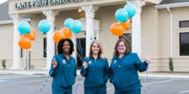 Smiling staff wearing blue scrubs holding teal and orange balloons in Hamlet