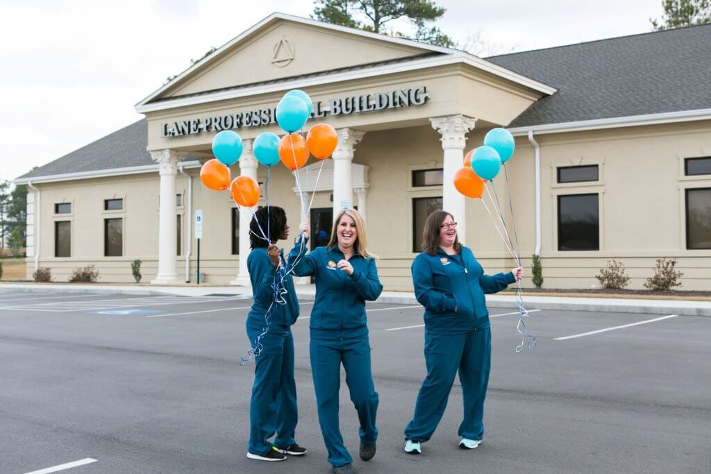 Dental assistants holding orange and teal balloons outside Hamlet NC dental office