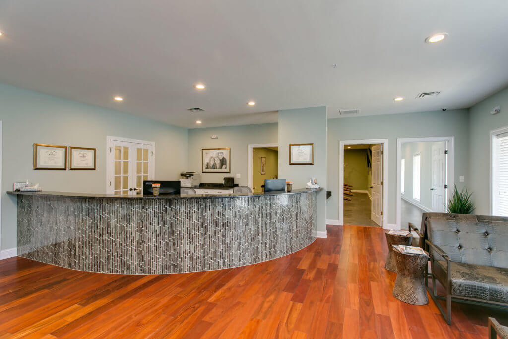 NC Oral Surgery + Orthodontics office in Dunn, NC with cherry hardwood floors interior and light gray checkin desk