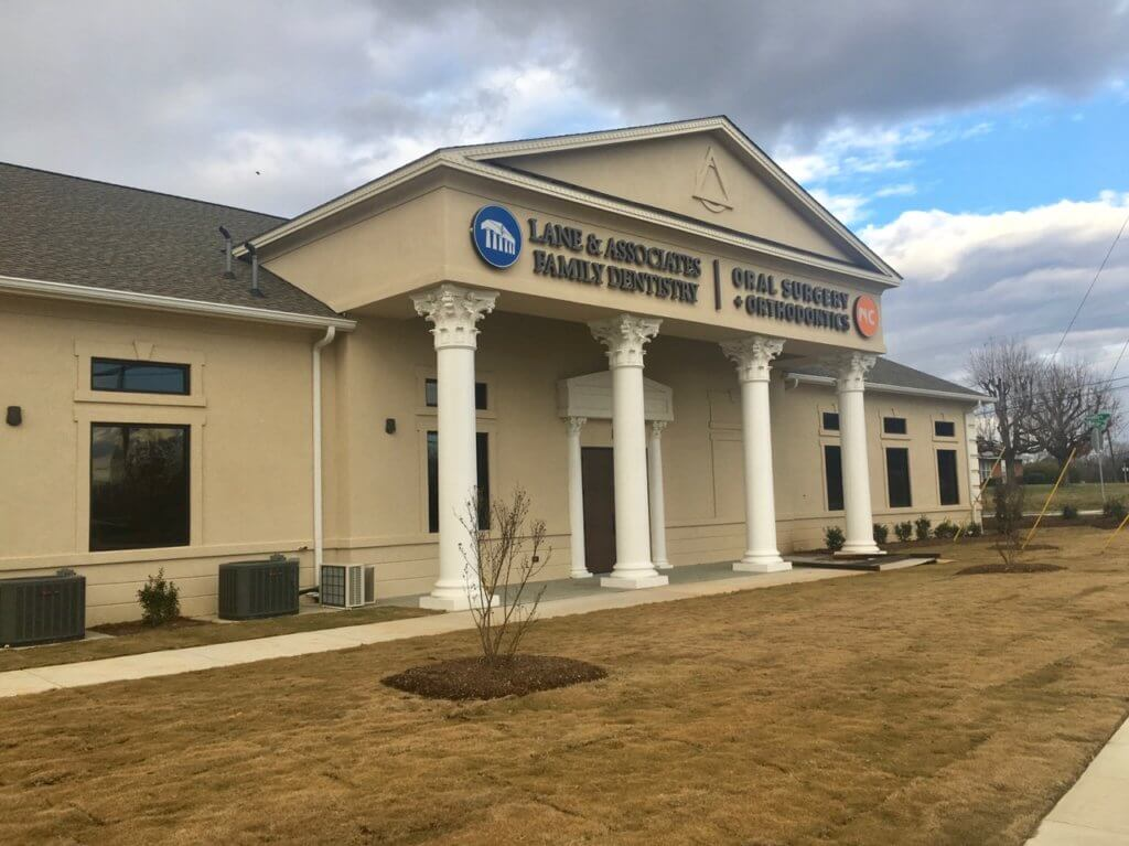 Winston Salem NC Orthodontist and Oral Surgeon office cream building with blue and orange sign
