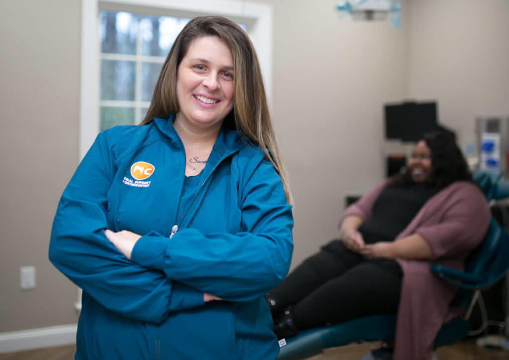 Oral Surgery Assistant smiling at camera with patient in turquoise dental chair behind her