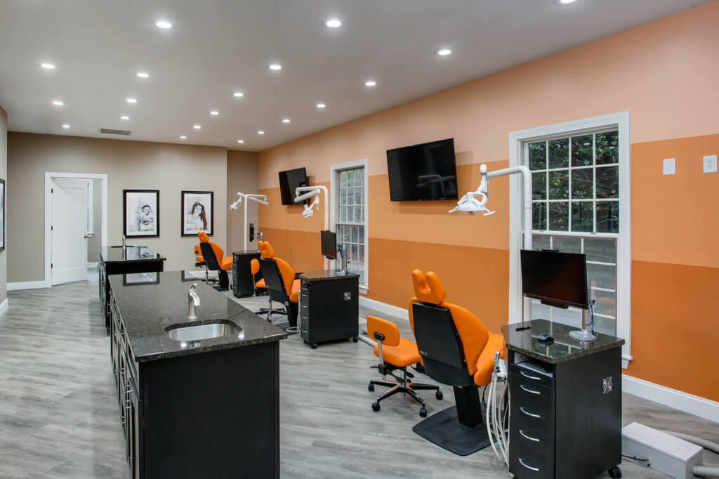 Southern Pines NC Orthodontic Bay with Orange striped fade wall and bright orange dental chairs
