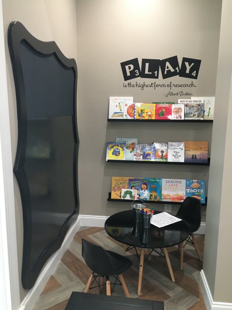 Kids corner with kids table, black dry erase board and markers, shelves filled with kids books, and PLAY written above shelf.