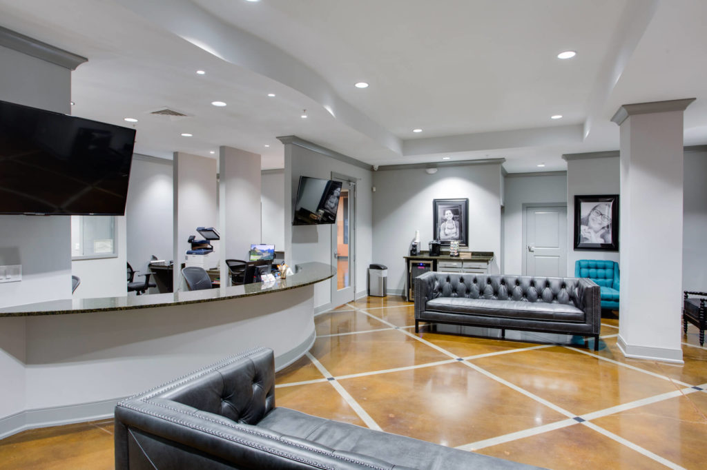 Cary Orthodontist interior Lobby area with gray leather couches and beautiful concrete floor