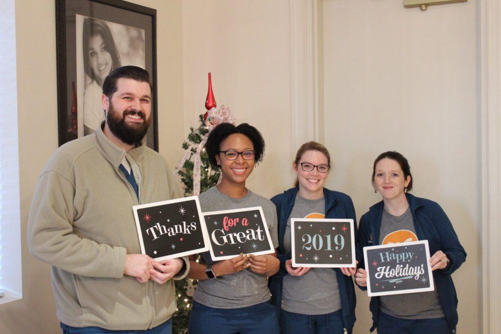 Garner NC Orthodontist team holding New Years signs