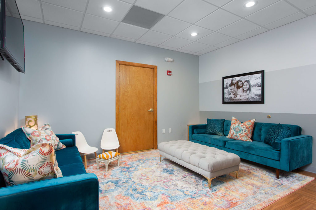Oral Surgery guest waiting area with couches and TV